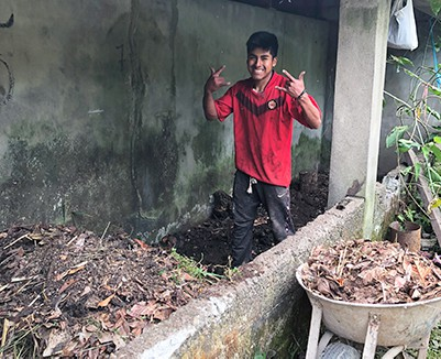 Photo of Marco with wheelbarrow making his first compost pile.